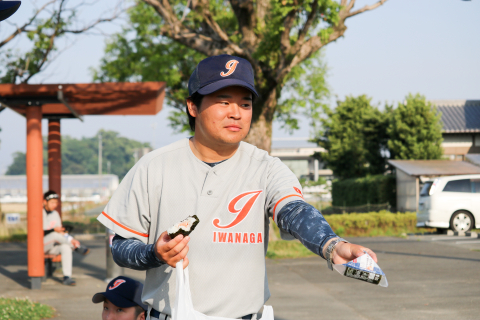 悔しさを隠しおにぎりを配る松本選手